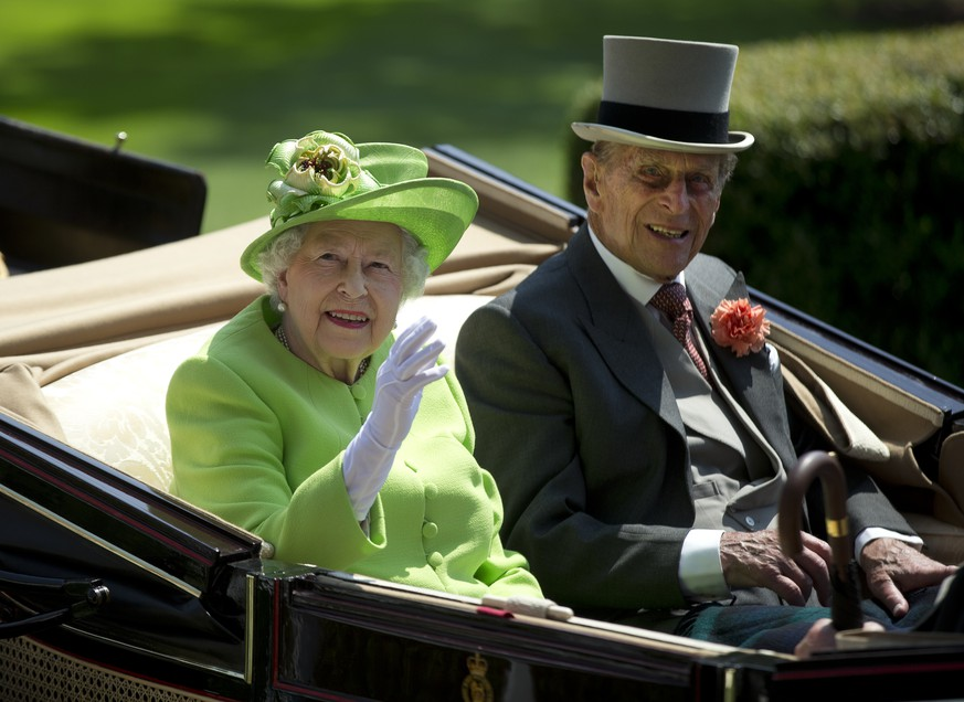 Britain's Queen Elizabeth II, left, waves to the crowd with Prince Philip at right, as they arrive by open carriage to the parade ring on the first day of the Royal Ascot horse race meeting in Ascot, England, Tuesday, June 20, 2017. (AP Photo/Alastair Grant)