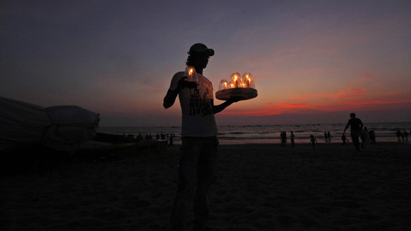 In this Monday, March 11, 2013 photograph, an Indian worker carries candles before putting them on restaurant tables at the Calangute beach on the Arabian Sea coast in Goa, India. Goa, known for its beaches, is a popular destination for Indian and foreign tourists. (AP Photo/ Rajesh Kumar Singh)