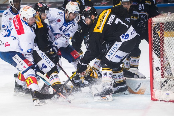 Zurich's player Mike Kuenzle, left, scores the 0-1 goal against Lugano's Philippe Furrer, right, and Lugano's Elvis Merzlikins, bottom, during the first match of the playoff final of the National League between HC Lugano and ZSC Lions, at the ice stadium Resega in Lugano, on Thursday, April 12, 2018. (KEYSTONE/Ti-Press/Samuel Golay)