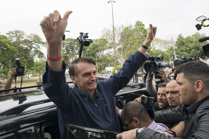 Presidential frontrunner Jair Bolsonaro, of the Social Liberal Party, flashes thumbs up to supporters after voting at a polling station in Rio de Janeiro, Brazil, Sunday, Oct. 7, 2018. Brazilians choose among 13 candidates for president Sunday in one of the most unpredictable and divisive elections in decades. If no one gets a majority in the first round, the top two candidates will compete in a runoff. (AP Photo/Leo Correa)