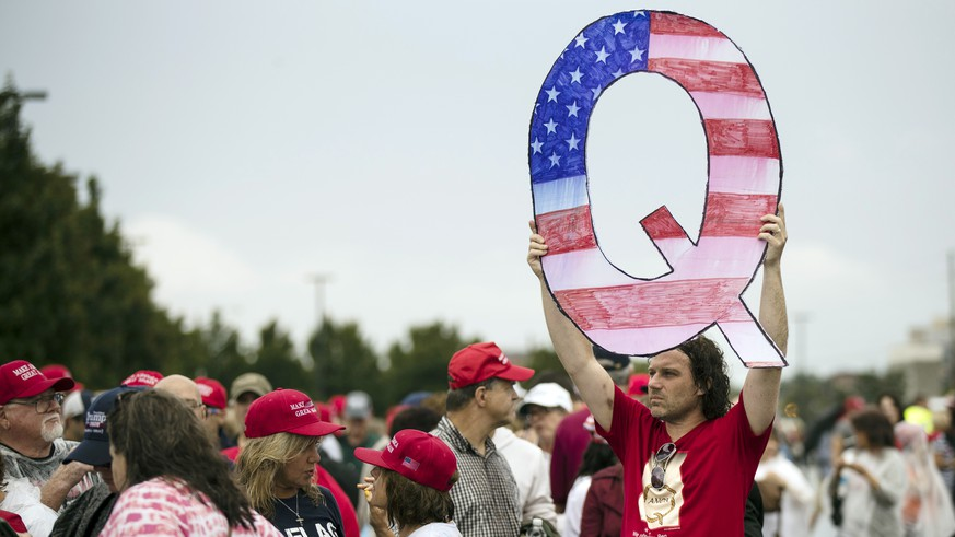 FILE - In this Aug. 2, 2018, file photo, David Reinert holding a Q sign waits in line with others to enter a campaign rally with President Donald Trump in Wilkes-Barre, Pa. A far-right conspiracy theory forged in a dark corner of the internet is creeping into the mainstream political arena. It's called QAnon, and it centers on the baseless belief that President Donald Trump is waging a secret campaign against enemies in the â??deep state.â?  (AP Photo/Matt Rourke, File)