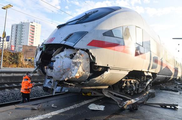 Mitarbeiter der Deutschen Bahn (DB) stehen am 17.02.2017 im Bahnhof Griesheim in Frankfurt am Main (Hessen) am zerstoerten Triebwagen eines ICE. Der leere Zug ist in der Nacht zum Freitag gegen einen Prellbock gefahren, entgleist und zum Teil auf einem Bahnsteig gelandet. Bei dem Unfall wurde niemand verletzt. (KEYSTONE/DPA/Arne Dedert)