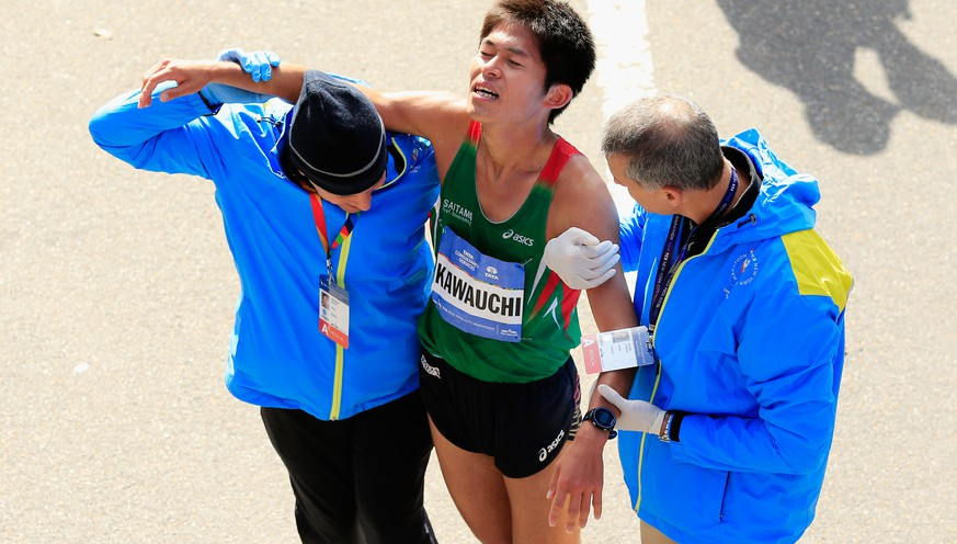 NEW YORK, NY - NOVEMBER 02:  Yuki Kawauchi of Japan is assisted after crossing the finsih line during the Pro Men's division during the 2014 TCS New York City Marathon in Central Park on November 2, 2014 in New York City.  (Photo by Alex Trautwig/Getty Images)