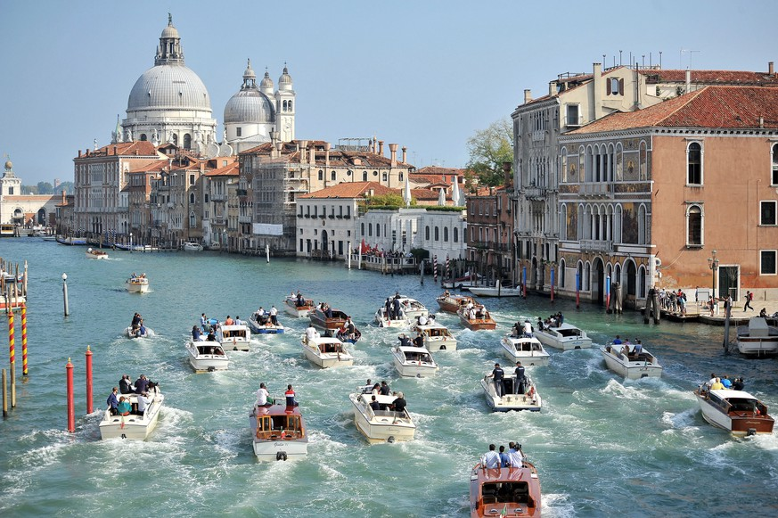 JAHRESRUECKBLICK 2014 – INTERNATIONAL – The boat carrying George Clooney and his wife Amal Alamuddin, is surrounded by media and security boats as they cruise the Grand Canal after leaving the Aman luxury Hotel in Venice, Italy, Sunday, Sept. 28, 2014. George Clooney married human rights lawyer Amal Alamuddin Saturday, the actor's representative said, out of sight of pursuing paparazzi and adoring crowds. (KEYSTONE/AP Photo/Luigi Costantini)