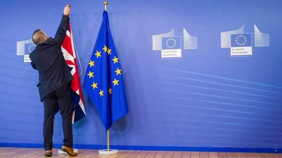 ZUR BREXIT-ABSTIMMUNG UEBER DEN VERBLEIB GROSSBRITANNIENS IN DER EUROPAEISCHEN UNION AM DONNERSTAG, 23. JUNI 2016, STELLEN WIR IHNEN FOLGENDES BILDMATERIAL ZUR VERFUEGUNG - An EU official hangs the Union Jack next to the European Union flag at the VIP entrance at the European Commission headquarters in Brussels on Tuesday, Feb. 16, 2016. British Prime Minister David Cameron is visiting EU leaders two days ahead of a crucial EU summit. (KEYSTONE/AP Photo/Geert Vanden Wijngaert)