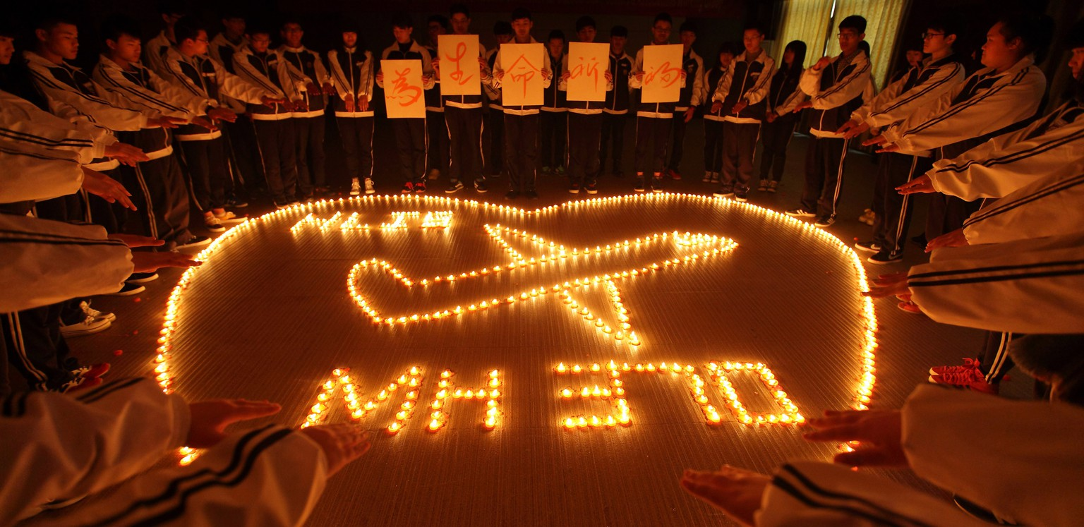 ZHUJI, CHINA - MARCH 10:  (CHINA OUT) Students from an international school in east China city Zhuji pray for the passengers onboard Malaysia Airlines flight MH370 by lighting candles on March 10, 2014 in Zhuji, China. Malaysia Airline flight MH370 from Kuala Lumpur to Beijing and carrying 239 onboard was reported missing after the crew failed to check in as scheduled while flying over waters between Malaysia and Ho Chi Minh City in Vietnam.  (Photo by ChinaFotoPress/ChinaFotoPress via Getty Images)