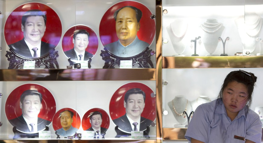 A vendor sells commemorative plates with images of Chinese President Xi Jinping and late Chinese leader Mao Zedong near Tiananmen Square in Beijing, China, Wednesday, June 4, 2014. Activists say this year has seen a longer and more restrictive clampdown on any attempts to commemorate the 25th anniversary of the bloody military suppression of pro-democracy protests centered on Tiananmen Square,  reflecting the increasingly conservative political atmosphere under President Xi Jinping, who took office last year. (AP Photo/Ng Han Guan)
