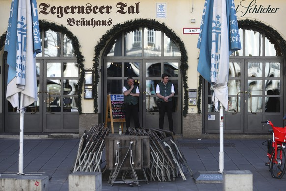 Waiters stand outside their Bavarian restaurant near the 'Marienplatz' downtown in Munich, Germany, Sunday, March 15, 2020. Germany has been slower than some of its neighbours to ban large gatherings, initially leaving the decision to local authorities as required by country's federal structure. For some, especially older adults and people with existing health problems, it can cause more severe illness, including pneumonia. (AP Photo/Matthias Schrader)