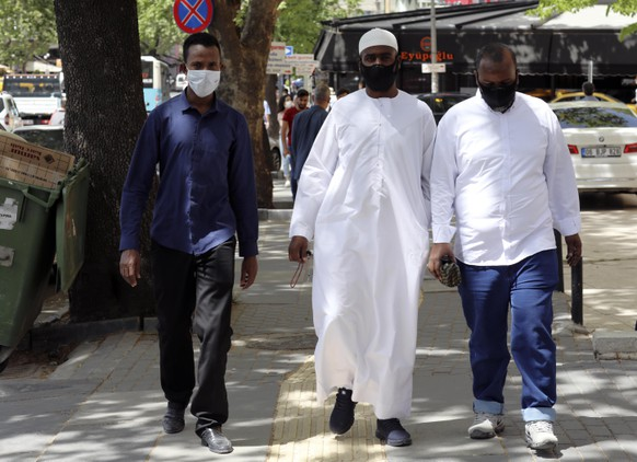 Somalian refugees living in Turkey, wearing face masks for protection against the coronavirus, walk in popular Tunali Hilmi Street, just hours before the start of a four-day curfew declared by the government in an attempt to control the spread of coronavirus, in Ankara, Turkey, Friday, May 15, 2020. Teenagers were able to leave their homes for the first time in 42 days on Friday, as their turn came for a few hours of respite from Turkey's coronavirus lockdowns.(AP Photo/Burhan Ozbilici)