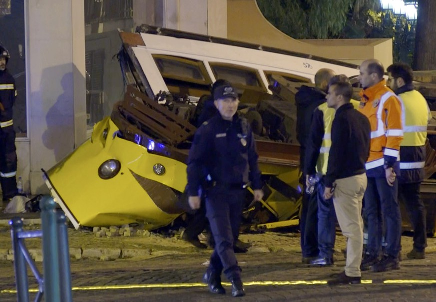 In this image taken from video, emergency service personnel work at the scene of a tram accident, Friday, Dec. 14, 2018, in Lisbon, Portugal. Portuguese emergency services say a Lisbon tram has derailed and flipped over, slightly injuring 28 people in a rush-hour accident. (Jorge Jerónimo /APTN via AP)