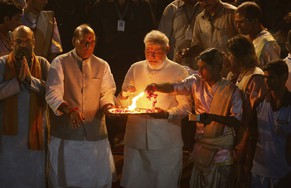 Opposition Bharatiya Janata Party (BJP) leader and India's next prime minister Narendra Modi perform evening Hindu rituals along with BJP President Rajnath Singh, as leader Amit Shah folds his hands in respect on the banks of the River Ganges in Varanasi, an ancient city revered by millions of devout Hindus, India, Saturday, May 17, 2014. Modi will be India's next prime minister, winning the most decisive victory the country has seen in more than a quarter century and sweeping the long-dominant Congress party from power, results showed Friday. An elaborately decorated platform was built for him to offer prayers on the banks of the river. Saffron flags fluttered above the flower bedecked platform and thousands of supporters and onlookers milled around to watch as Hindu priests chanted sacred verses and burnt incense. (AP Photo/Saurabh Das)