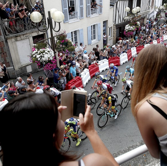 epa06885461 The peloton race through the streets while two spectators takes images of them on their mobile phones during the 7th stage of the 105th edition of the Tour de France cycling race, over 231km between Fougeres and Chartres, France, 13 July 2018.  EPA/YOAN VALAT