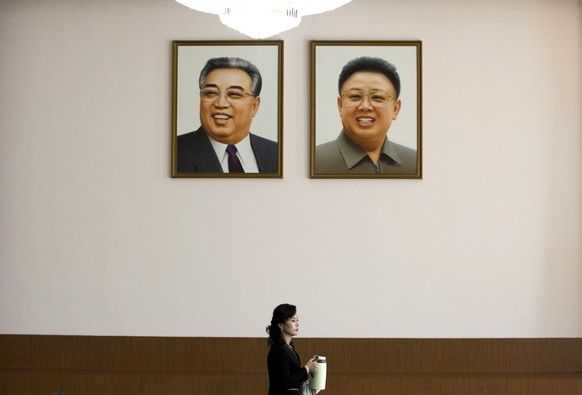 A woman holds a kettle while walking past photos of late North Korean leaders, Kim Il Sung, left, and Kim Jong Il displayed inside a room where a meeting is being held between Junichi Ihara, head of the Japanese Foreign Ministry's Asian and Oceanian Affairs Bureau and Song Il Ho, North Korea's ambassador in charge of normalizing relations with Japan, at the North Korean Embassy in Beijing, China Sunday, March 30, 2014. (AP Photo/Andy Wong)