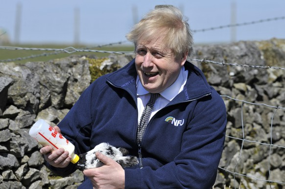 Britain's Prime Minister Boris Johnson feeds a lamb at Moor Farm in Stoney Middleton, England, Friday, April 23, 2021, as part of a Conservative party local election visit. (AP Photo/Rui Vieira, Pool)