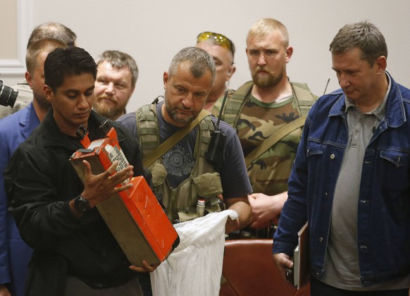 A Malaysian expert (L) examines a black box belonging to Malaysia Airlines flight MH17 during its handover from pro-Russian separatists, in Donetsk July 22, 2014. The remains of some of the 298 victims of the Malaysia Airlines plane downed over Ukraine were making their way to the Netherlands on Tuesday as Senior Ukrainian separatist leader Aleksander Borodai handed over the plane's black boxes to Malaysian experts. REUTERS/Maxim Zmeyev (UKRAINE - Tags: POLITICS TRANSPORT DISASTER CIVIL UNREST)