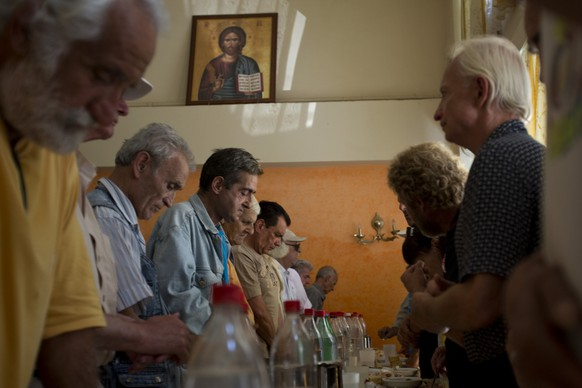 """Needy people pray before eating at the Church-run Galini charity's soup kitchen in central Athens on Monday, July 6, 2015. Greece's finance minister has resigned following Sunday's referendum in which the majority of voters said """"no"""" to more austerity measures in exchange for another financial bailout. (AP Photo/Emilio Morenatti)"""