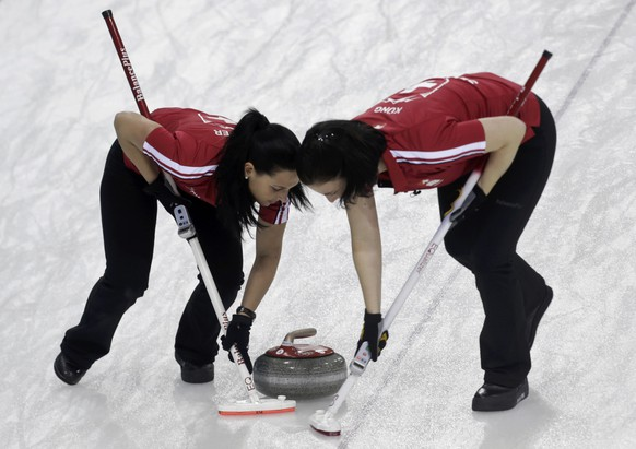 Switzerland's third Carmen Schaefer and second Carmen Kueng (R) sweep the stone during their women's curling round robin game against Denmark at the Sochi 2014 Winter Olympic Games in the Ice Cube Curling Center February 11, 2014. REUTERS/Ints Kalnins (RUSSIA  - Tags: SPORT CURLING OLYMPICS)