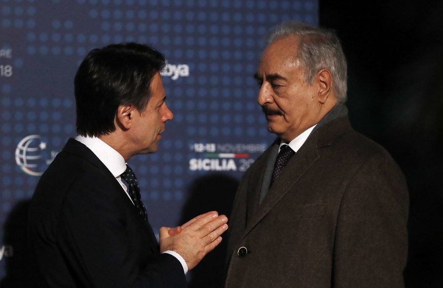 Gen. Khalifa Hifter, commander of the self-styled Libyan National Army, right, talks with Italian Prime Minister Giuseppe Conte in Palermo, Italy, Monday, Nov. 12, 2018. Representatives of Libya's quarrelling factions and of countries keen on stabilizing the North African nation started meetings in Sicily Monday, as Italy encourages a political settlement that could bolster the fight against Islamic militants and stop illegal migrants from crossing the Mediterranean to Europe's southern shores. (AP Photo/Antonio Calanni)