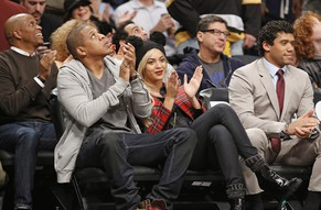 Entrepreneur and musician Jay Z, left, sits beside his wife, singer Beyonce, and Seattle Seahawks quarterback Russell Wilson during the Brooklyn Nets NBA basketball game against the Philadelphia 76ers at the Barclays Center, Monday, Feb. 3, 2014 in New York. (AP Photo/Kathy Willens)