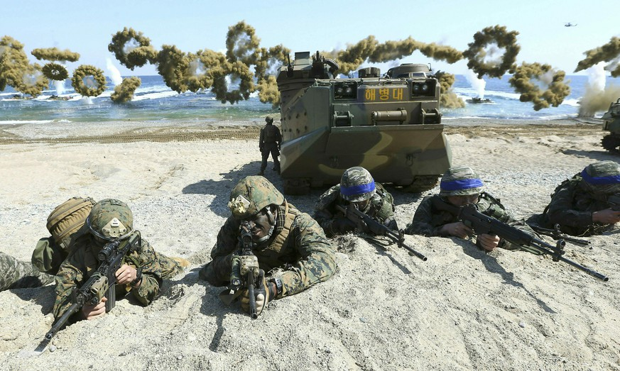 FILE - In this March 12, 2016, file photo, Marines of the U.S., left, and South Korea, wearing blue headbands on their helmets, take positions after landing on a beach during the joint military combined amphibious exercise, called Ssangyong, part of the Key Resolve and Foal Eagle military exercises, in Pohang, South Korea. Ahead of the second summit between U.S. President Donald Trump and North Korean leader Kim Jong Un, some observers say there is an uncertainty over the future of the decades-long military alliance between Washington and Seoul. (Kim Jun-bum/Yonhap via AP, File)