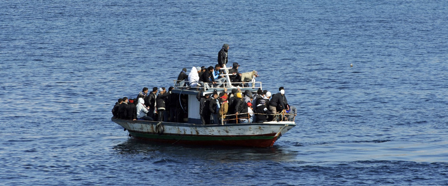 FILE - In this file photo taken on Feb. 13, 2011, a boatload of would-be migrants believed to be from North Africa is seen moments before being rescued by the Italian Coast Guard in the waters off the Sicilian island of Lampedusa, Italy. Large and barely seaworthy wooden fishing boats carrying loads of many more paying migrants are so highly valued by Libyan smugglers that armed men recently showed up in speedboats to recover them for reuse after migrants were saved by the European Union's Frontex border patrol mission. As the number of migrants heading to Europe soars, the boats that get them there are the smuggler's key commodity - one that's incredibly difficult for authorities to prevent them from obtaining. (AP Photo/Daniele La Monaca, File)