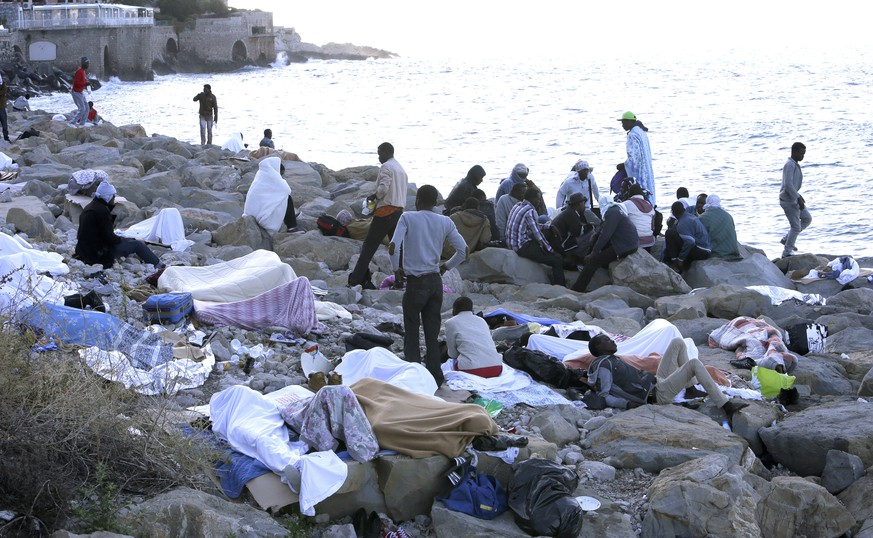 Migrants sit together after waking up while the rest sleep on the rocky beach at the France's Mediterranean boarder with Italy near Menton, southeastern France, Monday, June 15, 2015. French border police blocked border crossings last week, citing the influx of migrants, principally from Eritrea and Sudan, and about 200 would-be refugees have refused to leave the rocks of Ventimiglia, Italy, just a few kilometers from the swank resorts of Nice and Saint-Jean-Cap-Ferrat on the French Riviera. (AP Photo/Lionel Cironneau)