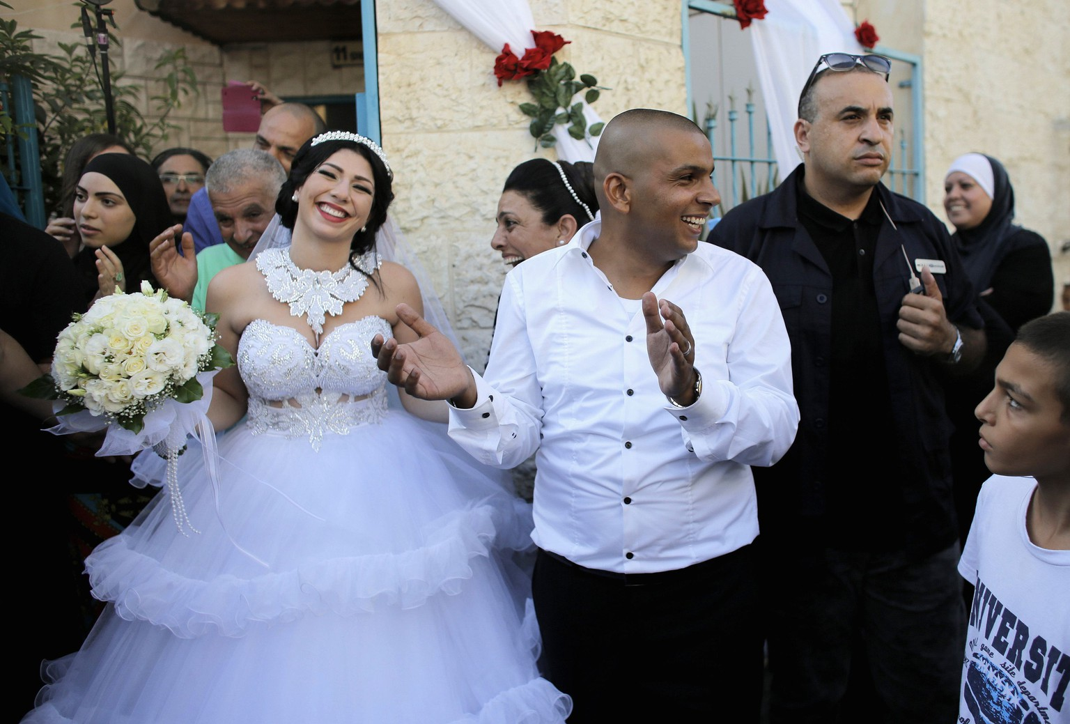 Groom Mahmoud Mansour, 26, (C) and his bride Maral Malka, 23, celebrate with friends and family before their wedding in Mahmoud's family house in Jaffa, south of Tel Aviv August 17, 2014. Israeli police on Sunday blocked more than 200 far-right Israeli protesters from rushing guests at the wedding of a Jewish woman and Muslim man as they shouted
