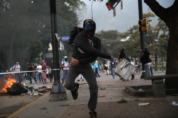 CARACAS, VENEZUELA - MARCH 06:  A protester throws a rock at Venezuelan security forces during an anti-government demonstration on March 6, 2014 in Caracas, Venezuela. Three weeks of protests against the federal government have shaken the country as business in much of the nation has come to a standstill.  (Photo by John Moore/Getty Images)