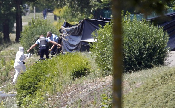 French crime scene investigators and Gendarmes are seen at work next to a black plastic sheet outside a gas company site at the industrial area of Saint-Quentin-Fallavier, near Lyon, France, June 26, 2015. A decapitated head covered in Arabic writing was found at a a site belonged to Air Products, a U.S.-based industrial gases technology company, in southeast France on Friday, police sources and French media said, after two assailants rammed a car into the premises, exploding gas containers.    REUTERS/Emmanuel Foudrot