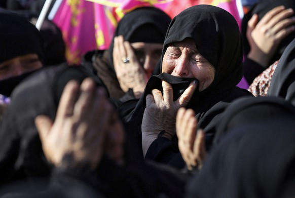 Shiite pilgrims react during the Muslim festival of Arbaeen in Karbala, 50 miles (80 kilometers) south of Baghdad, Iraq, Tuesday, Dec. 24 , 2013. The holiday marks the end of the forty day mourning period after the anniversary of the 7th century martyrdom of Imam Hussein the Prophet Muhammad's grandson. (AP Photo/Hadi Mizban)