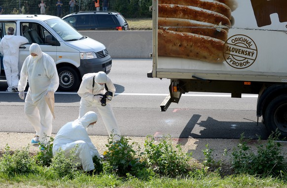 epa04900517 Forensic experts investigate a truck in which refugees were found dead as it stands on freeway autobahn A4 between Parndorf and Neusiedl, Austria, 27 August 2015. According to reports, some 50 refugees were found dead in the lorry parked at the autobahn. It cannot be confirmed if the dead suffocated in the truck, as some media have reported. The lorry was discovered by highway workers who called police. The driver has disappeared, according to media reports.  EPA/ROLAND SCHLAGER