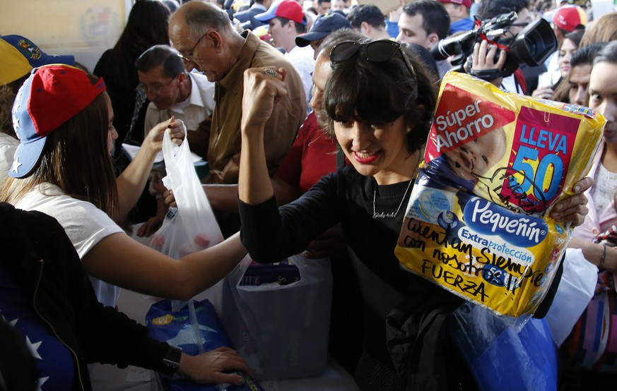 A Venezuelan woman gestures as she donates a pack of diapers during the