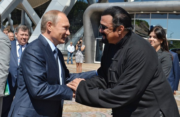 epa05615777 A picture dated 04 September 2015 and released on 03 November 2016 shows Russian President Vladimir Putin (L) shaking hands with US actor Steven Seagal (R) while visiting an oceanarium at the Russky Island, near Vladivostok, Russia. According to reports from 03 November 2016, Russian President Vladimir Putin signed a decree granting citizenship to actor and mixed martial arts expert Steven Seagal following his repeated requests.  EPA/ALEXEI DRUZHININ / SPUTNIK / KREMLIN POOL MANDATORY CREDIT