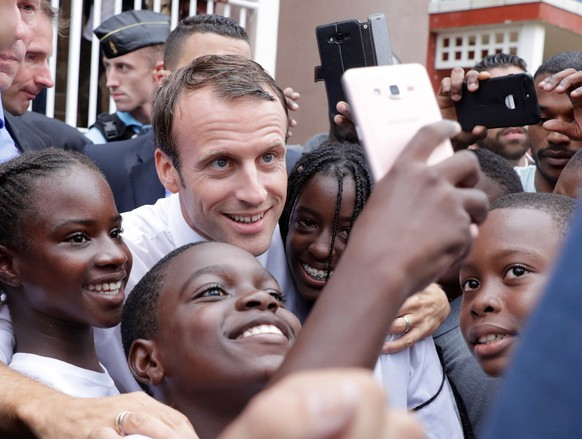 epa07059212 French president Emmanuel Macron takes sefies with children in Quartier d'Orleans, 29 September 2018, (issued 30 September 2018 on the French Caribbean island of Saint-Martin, during a trip in the French West Indies, one year after Hurricanes Irma and Maria damaged the Island.  EPA/THOMAS SAMSON / POOL MAXPPP OUT