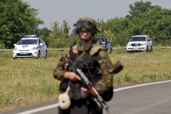 epa04335397 An armed separatist in military attires stand guard as they block the road for the passage of the Organization for Security and Co-operation in Europe (OSCE) members between Donetsk and Slavonst in Ukraine, 30 July 2014. The OSCE members and experts were again not able to get to the crash site of the Malaysian Boeing flight MH17. The Boeing 777 was carrying 298 people from Amsterdam to Kuala Lumpur when it was shot down near Ukraine's border with Russia on July 17.  EPA/EVERT-JAN DANIELS