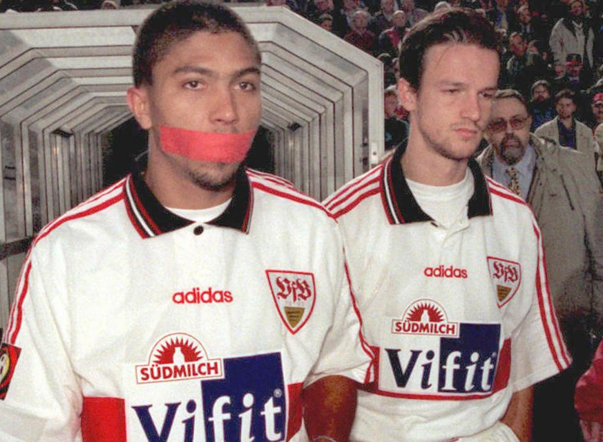 Giovane Elber (L) of VfB Stuttgart comes of the cubicles for the second half with a piece of tape over his mouth during the German Bundesliga match between Stuttgart and 1860 Munich at Gottlieb-Daimler stadium late 27 March,1997. Elber, who was booked because of grumble in the 26th minute, expressed his displeasure at the referee's decision until he was as sent off in 77th minute after receiving a yellow-red car for foul play. Elber's teammate Fredy Bobic (R) as well was booked after grumble.(EPA/DPA/Rolf H.Seybolt)