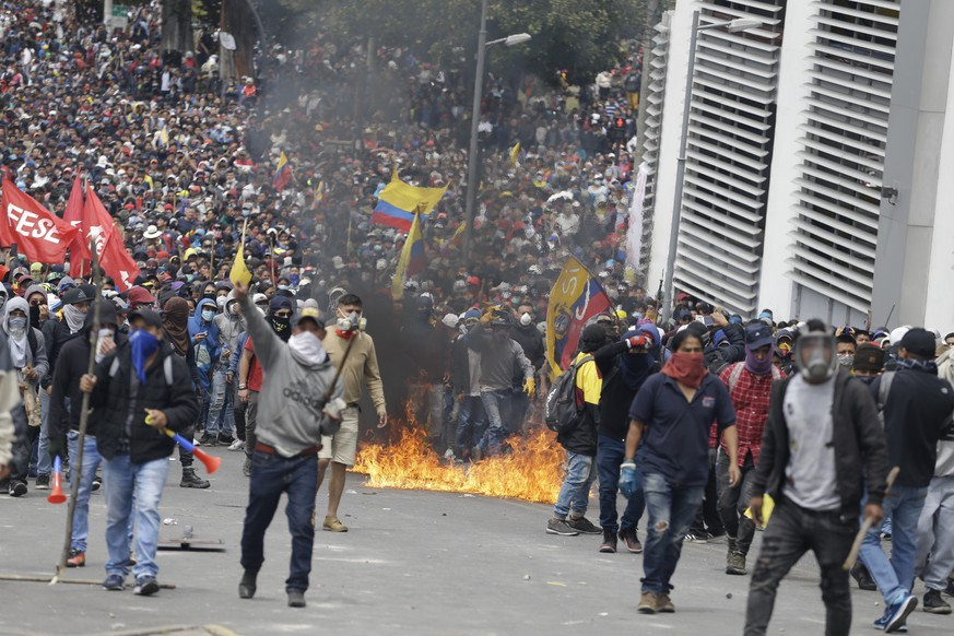 Enraged anti-government demonstrator gather during clashes with the police as they protest against President Lenin Moreno and his economic policies, in Quito, Ecuador, Tuesday, Oct. 8, 2019. Ecuador has endured days of popular upheaval since President Moreno scrapped fuel price subsidies, a step that set off protests and clashes across the South American country. (AP Photo/Fernando Vergara)