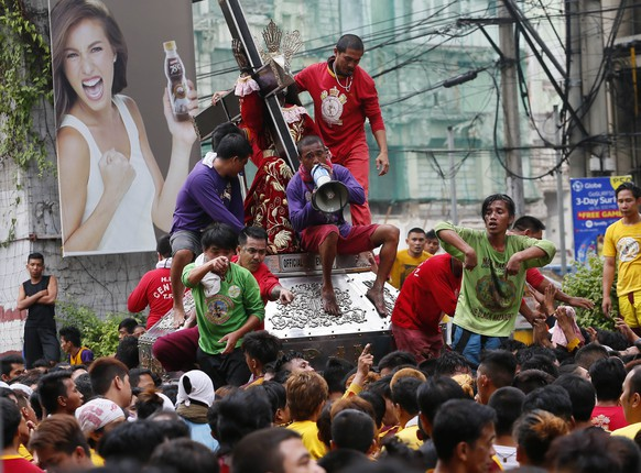 Filipino Catholic devotees jostle to get closer to the image of the Black Nazarene during a thanksgiving procession on New Year's eve in Manila, Philippines, Thursday, Dec. 31, 2015. The procession was held on New Year's eve amidst heightened alert by the Philippine National Police for the Yuletide season. (AP Photo/Bullit Marquez)