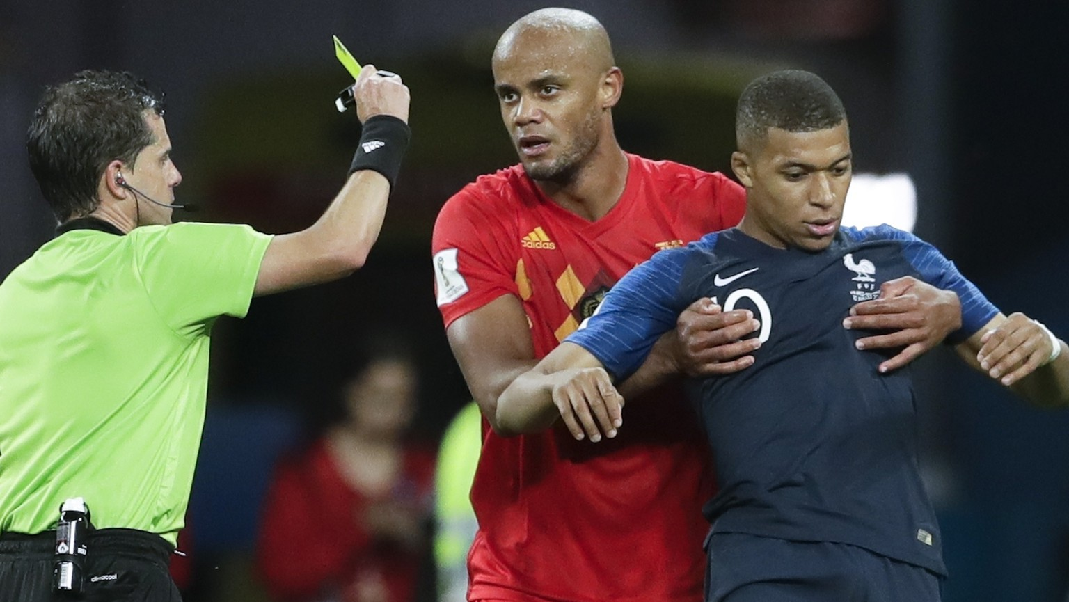 Referee Andres Cunha from Uruguay shows a yellow card to France's Kylian Mbappe during the semifinal match between France and Belgium at the 2018 soccer World Cup in the St. Petersburg Stadium, in St. Petersburg, Russia, Tuesday, July 10, 2018. (AP Photo/Petr David Josek)