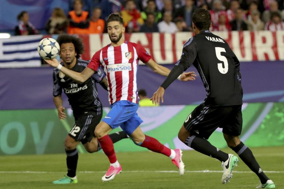 epa05955921 Atletico Madrid's Yannick Ferreira Carrasco (C) vies for the ball with Real Madrid's Marcelo (L) and Raphael Varane (R) during the UEFA Champions League semifinal second leg match between Atletico Madrid and Real Madrid at the Vicente Calderon stadium, in Madrid, Spain, 10 May 2017.  EPA/JUANJO MARTIN