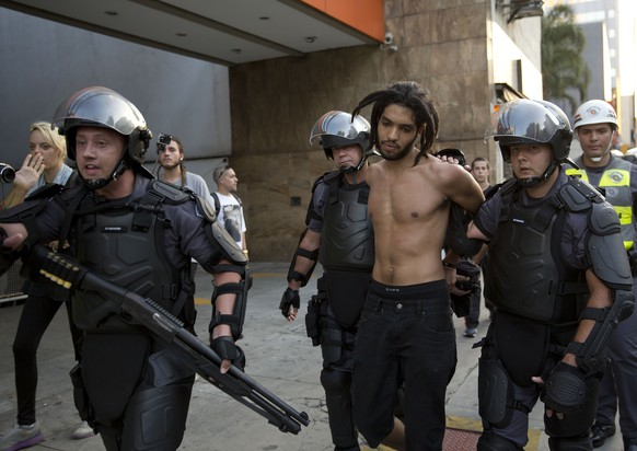 Police officers detain a demonstrator during a protest against a price hike of public transportation fares in Sao Paulo, Brazil, Friday, Jan. 9, 2015. A few thousand people took to the streets of Brazil's biggest city to protest over an 18-cent increase in bus and subway fares. (AP Photo/Andre Penner)