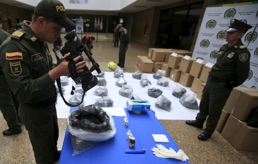 Colombian anti-narcotics police officers film packs of cocaine at the police building in Bogota, Colombia September 7, 2015. Police in Colombia and Mexico have seized more than two tonnes of cocaine after a drug-sniffing dog alerted authorities in Bogota to the narcotics, which had been dyed black and falsely registered as an ingredient in printer cartridges, the Colombian police said on Monday. REUTERS/ John Vizcaino