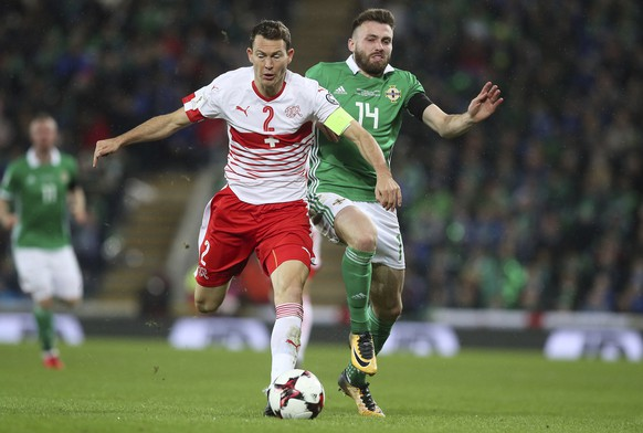 Switzerland's Stephan Lichtsteiner, left, and Northern Ireland's Stuart Dallas battle for the ball during the World Cup qualifying play-off first leg soccer match between Northern Ireland and Switzerland at Windsor Park in Belfast, Northern Ireland, Thursday Nov. 9, 2017. (Brian Lawless/PA via AP)
