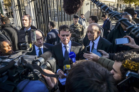 French Prime Minister Manuel Valls (3rdL) stands with ministers, from L- R, Justice Minister Christiane Taubira, Interior Minister Bernard Cazeneuve and French Defense Minister Jean-Yves Le Drian as they speak to journalists after they visited the psychological help center at the Ecole Militaire to assist survivors and the families of victims in Paris, France, November 15, 2015, two days after a series of fatal shootings in the French capital. REUTERS/Christophe Petit Tesson/Pool