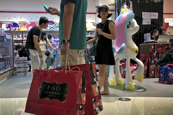 FILE - In this June 1, 2019, photo, file a man carries a paper bags containing toys purchased from the FAO Schwarz as people shop at the newly open FAO Schwarz toy store at the capital city's popular shopping mall in Beijing. Caught in the crossfire of a trade war, American businesses operating in the China say they've been hurt by the hostilities between the world's two biggest economies and are facing increasingly unfair competition from Chinese firms. (AP Photo/Andy Wong, File)