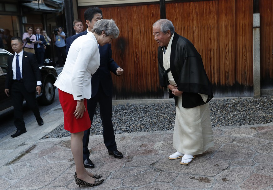 Britain's Prime Minister Theresa May, left, flanked by Japan's Prime Minister Shinzo Abe (behind May) is welcomed by Master of Tea Ceremony Sen Sosa, right, upon her arrival for a tea ceremony at the Omotesenke Fushin'an in Kyoto, western Japan, Wednesday, Aug. 30, 2017. (Kim Kyung-hoon/Pool Photo via AP)
