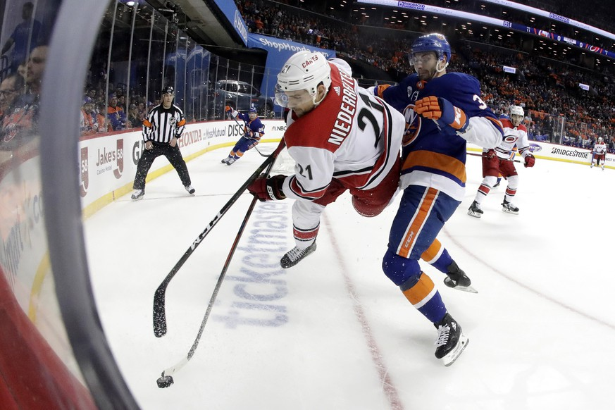 Carolina Hurricanes right wing Nino Niederreiter (21), of Switzerland, goes airborne while taking a hit from New York Islanders defenseman Adam Pelech (3) during the first period of Game 1 of an NHL hockey second-round playoff series, Friday, April 26, 2019, in New York. (AP Photo/Julio Cortez)