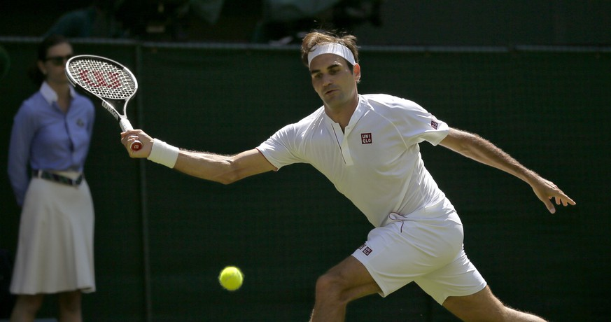 Roger Federer of Switzerland returns to Serbia's Dusan Lajovic during their Men's Singles first round match at the Wimbledon Tennis Championships in London, Monday July 2, 2018. (AP Photo/Tim Ireland)