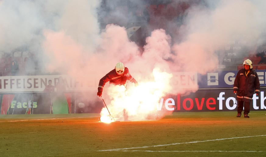 Firefighters remove light flares launching by Grasshopper's supporters, during the Super League soccer match of Swiss Championship between FC Sion and Grasshoppers Club, at the Stade de Tourbillon stadium, in Sion, Switzerland, Saturday, March 16, 2019. (KEYSTONE/Salvatore Di Nolfi)