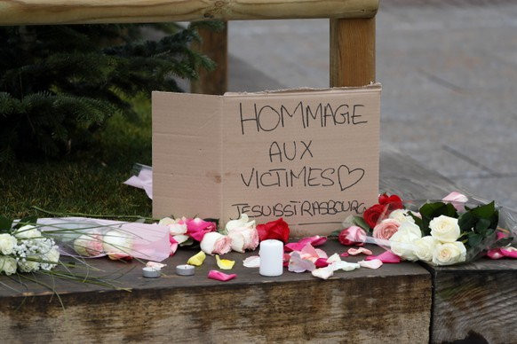 epa07225743 Flowers, candles and a sign reading 'Tribute to the victims - Je Suis Strasbourg' are left where a person was killed during the Christmas Market shooting in Strasbourg, France, 12 December 2018. According to latest reports, three people were killed and several injured when a gunman opened fire at the Strasbourg Christmas market a day earlier. The suspect is reported to be at large and the motive for the attack is still unclear.  EPA/RONALD WITTEK
